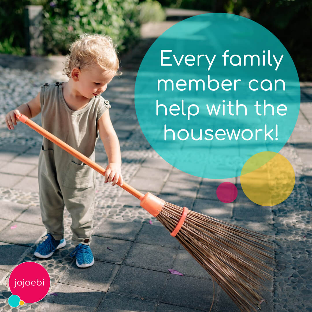 toddler sweeping the yard with a broom as he helps the family with the housework