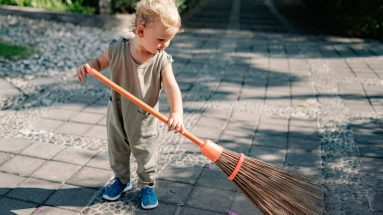 toddler sweeping the yar with a broom