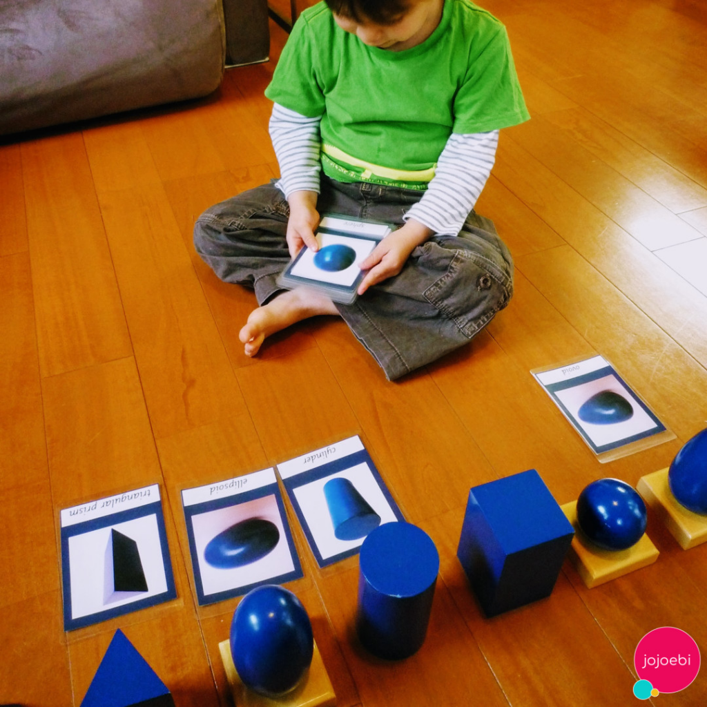 A child is learning shapes through Montessori 3 part cards
