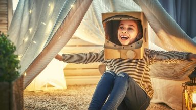 A photo of a little girl in a black and white striped shirt and blue jeans, wearing a cardboard astronaut helmet, playing in a tent made of bed-sheet in a room. This picture is posted in 'How to spark kids interests in learning new things' on jojoebi.com