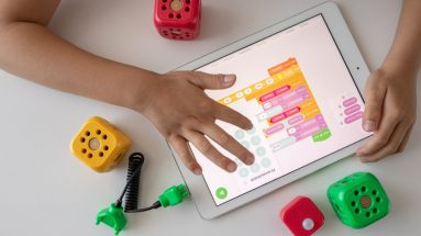 child playing on an ipad with some coding blocks.