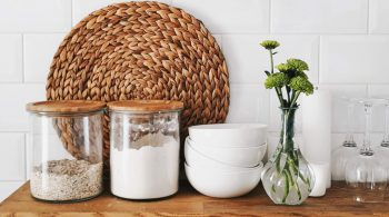 kitchen shelf with food in jars, woven mat and white bowls on display