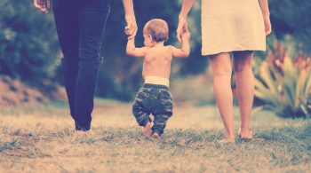parents walking holding their toddlers hand taking baby steps