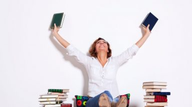 woman with her hands in the air holding books