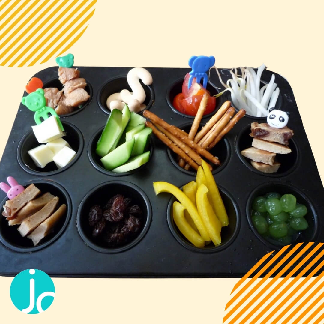 a muffin tin dinner containing Mini chicken kebabs, letter crackers, mini tomatoes, bean sprouts, pretzel sticks, cucumber sticks,  cheese cubes, raisins, yellow pepper, grapes.