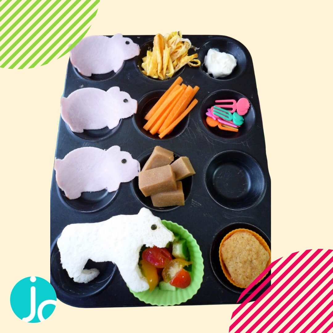 3 little pigs themed muffin tin meal, ham shaped as pigs, bread wolf and vegetables