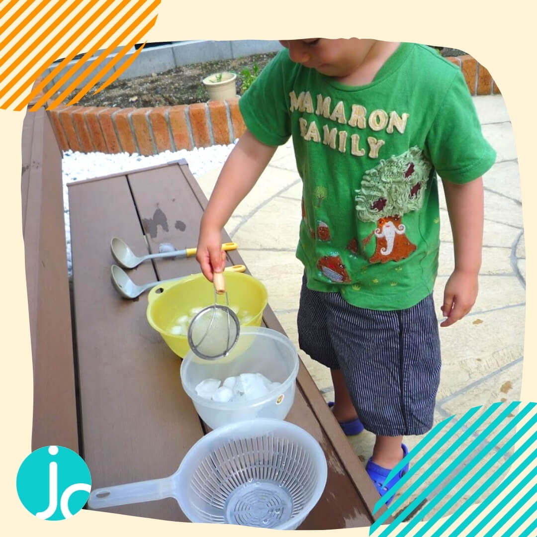 a toddler transferring ice into different bowls as a way to stay cool in the hot summer
