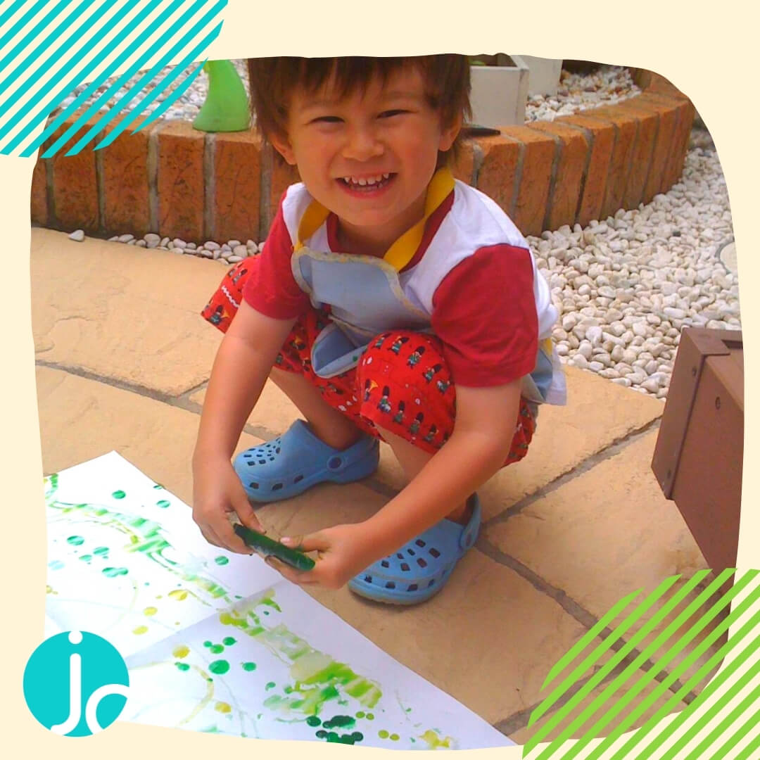a small boy painting with coloured ice