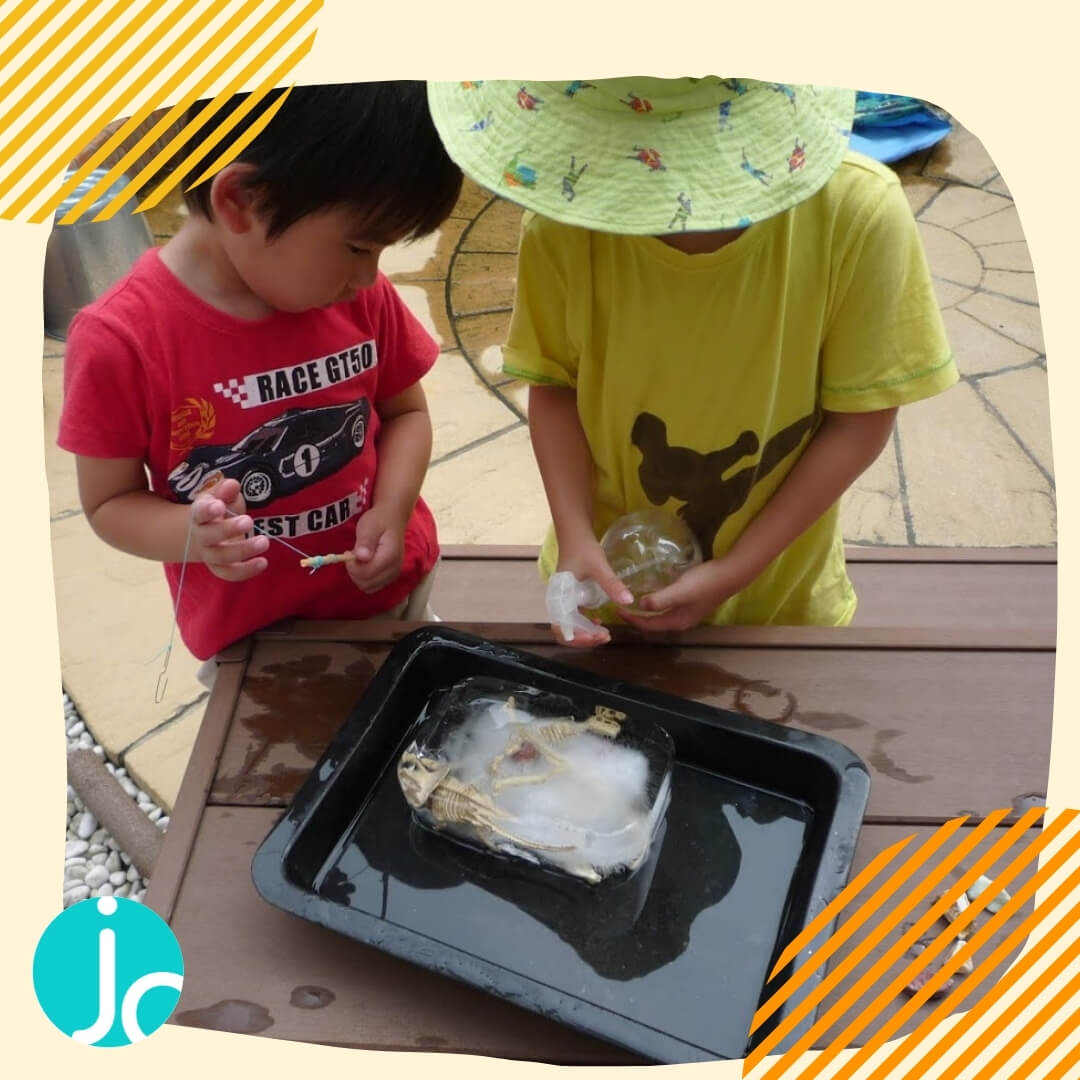 Kids staying cool and busy when it's hot by digging plastic dinosaur bones from a block of ice