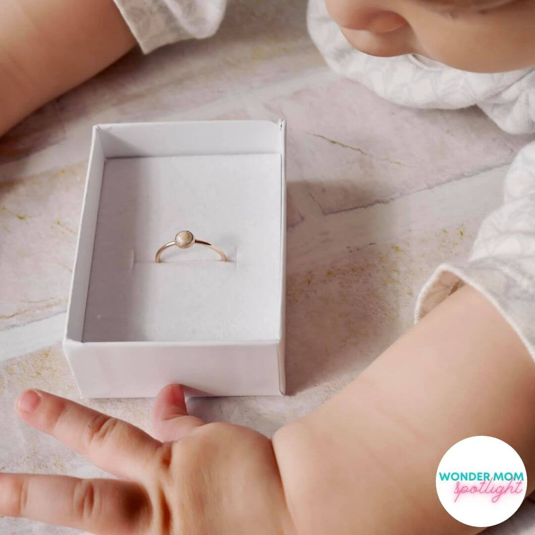 baby hands around a box with a ring