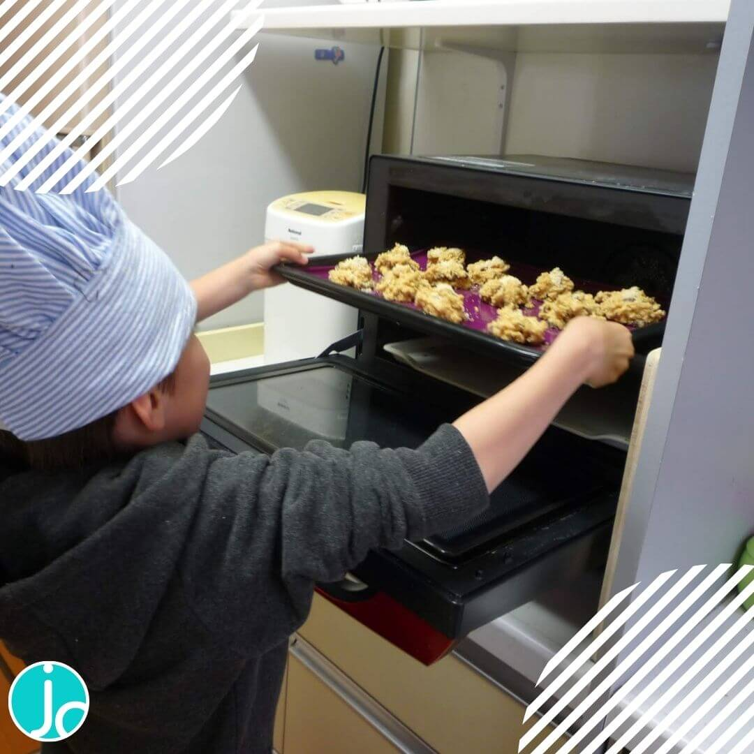 Boy placing cookies tray in oven
